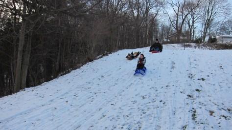 kids sledding on snow covered hill