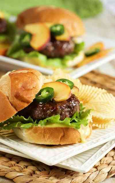 Hamburger topped with peaches and jalapenos alongside chips on a plate