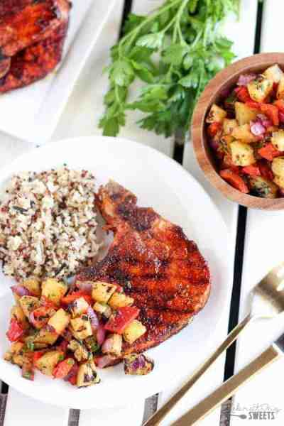 Grilled sweet and smokey pork chops with rice and potatoes on plate