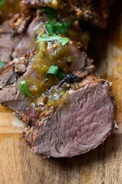 Salsa verde pork tenderloin slices on cutting board