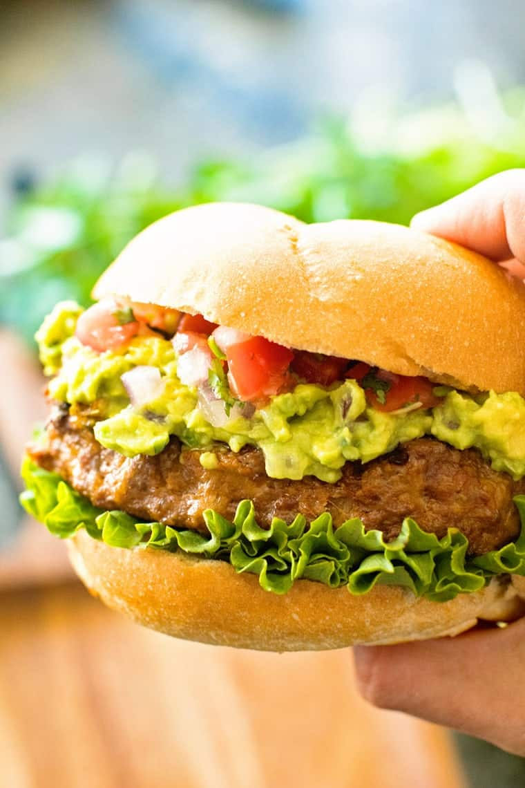 A hand holding a taco burger.