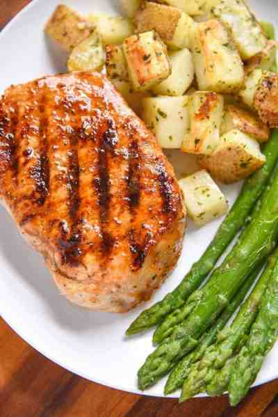 Marinated pork chop, potatoes, and asparagus on plate