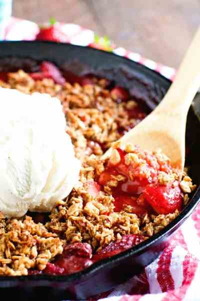 A black cast iron skillet filled with a hot bubbly strawberry crips. A wooden spoon is serving up a spoonful topped with vanilla ice cream.