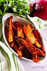 Seasoned sweet potato wedges in white bowl