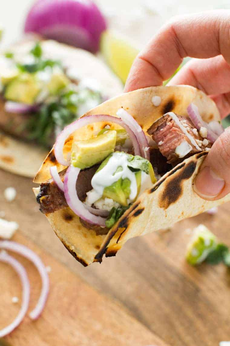 Steak Tacos topped with avocado, red onion and sour cream.