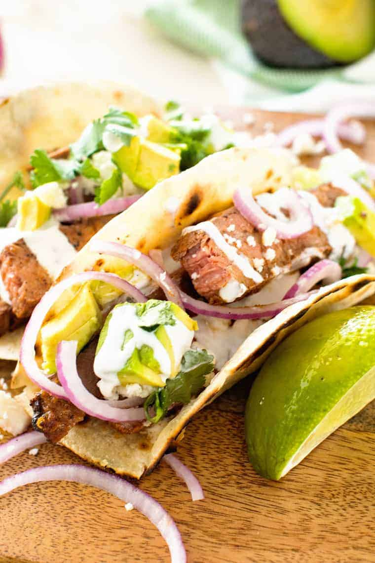 Flank steak tacos lined up on a wooden curling board topped with cilantro, red onion, avocado and a squeeze of lime.