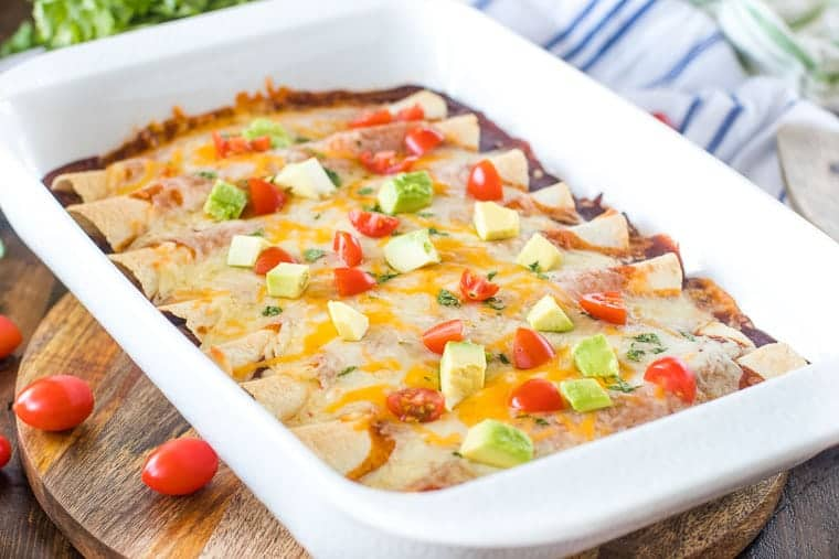 White casserole dish with pulled pork enchiladas