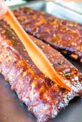honey garlic smoked ribs being brushed with sauce
