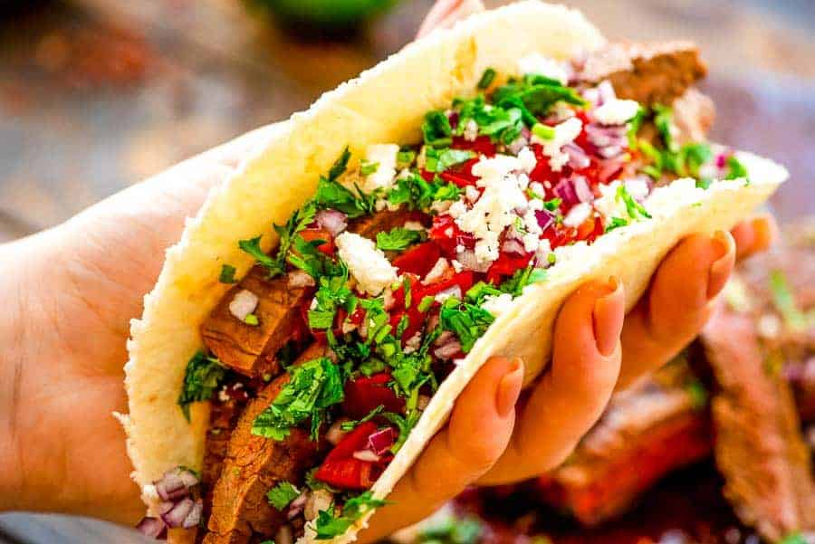 Hand holding Flank Steak Tacos