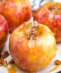 Grilled Baked Apples with caramel and nuts on a white plate
