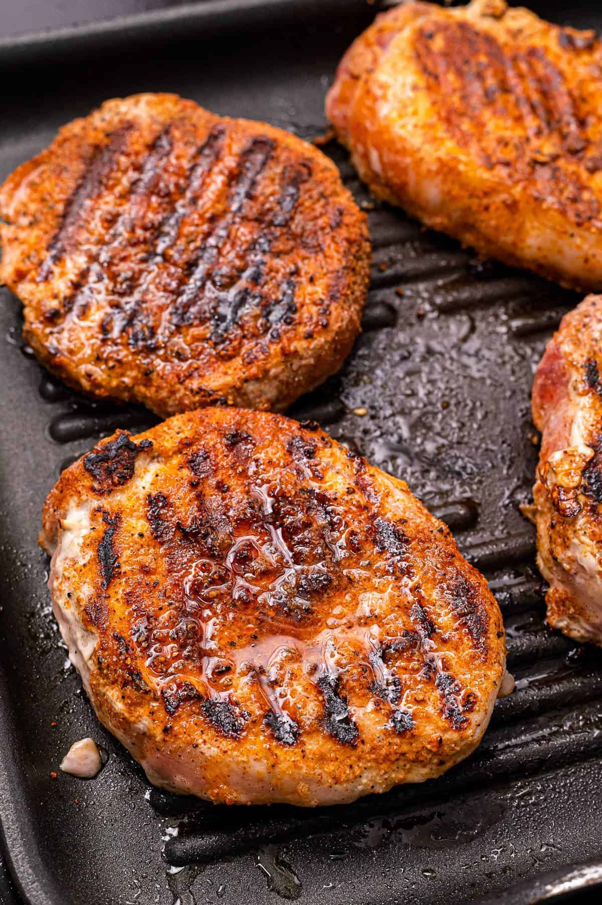 A grill pan with seasoned pork chops on it