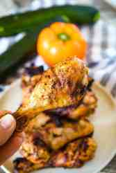 Fingers holding grilled chicken leg with plate of chicken legs in background along with orange pepper and zucchinis