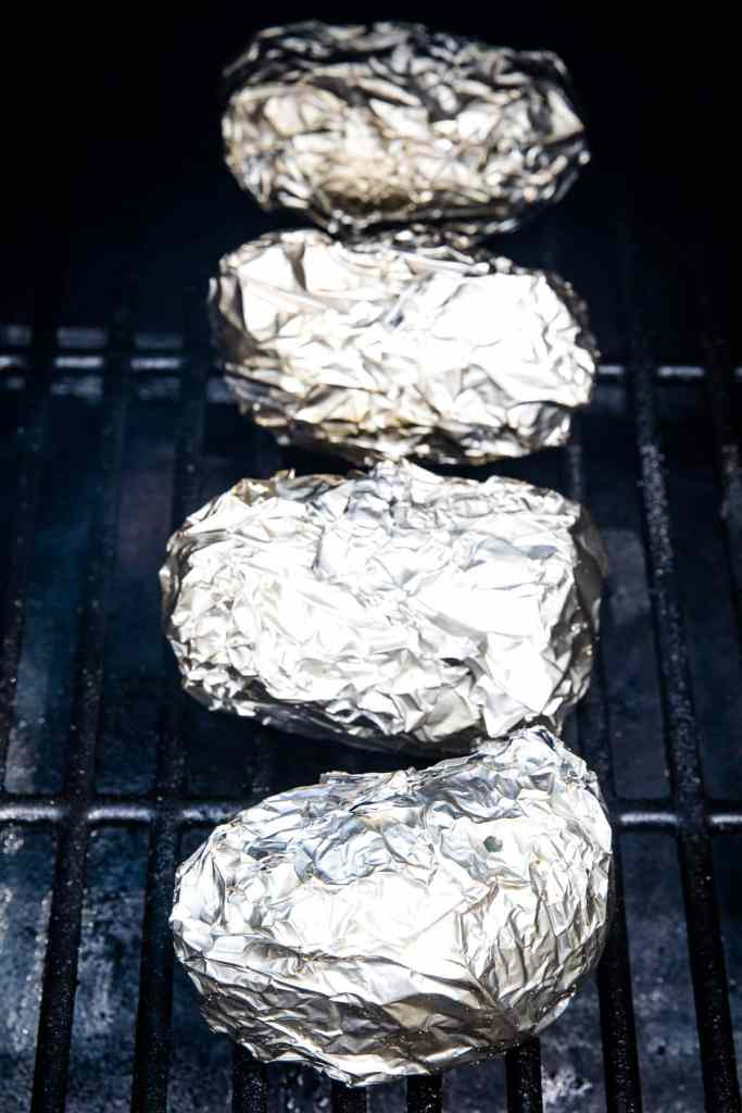 Potatoes wrapped in aluminum foil sitting on the smoker rack.
