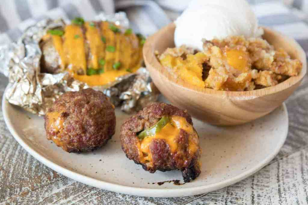Image showing jalapeno meatballs, hasselback potatoes and peach dump cake on plate