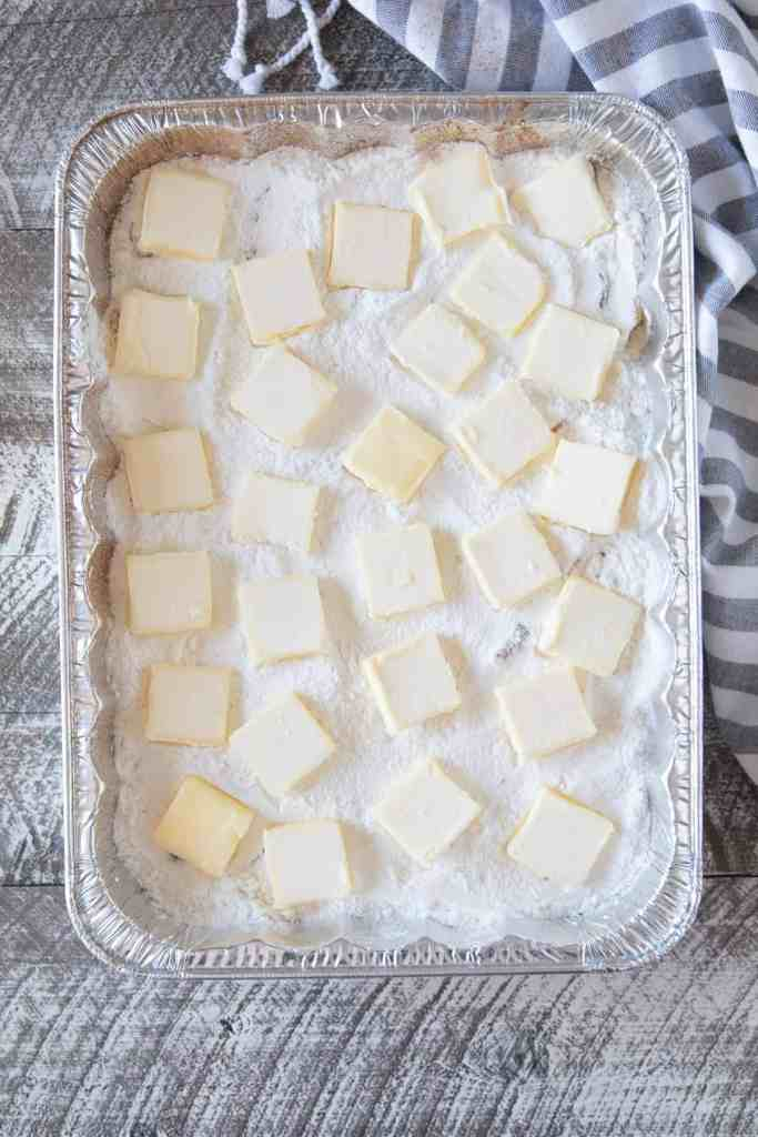 Slabs of butter evenly placed on top of cake mix in a dump cake.