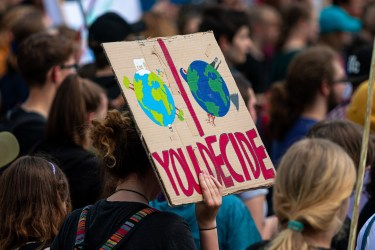 """Environmental protester at a demonstration holding a sign with a clean Earth and a dirty Earth and the slogan """"You Decide"""""""