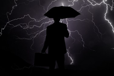 Silhouette of a businessman outside in a thunderstorm holding an umbrella and brielfase with lightning flashing behind him