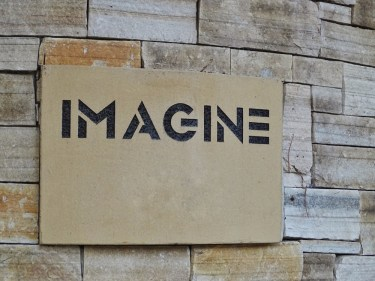 "Sign that says ""imagine"" fixed to a stone wall"