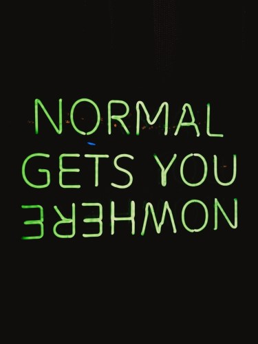 """Green neon sign with the slogan """"Normal gets you nowhere"""""""