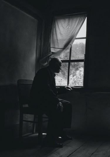 Elderly man in poor housing sitting by a window