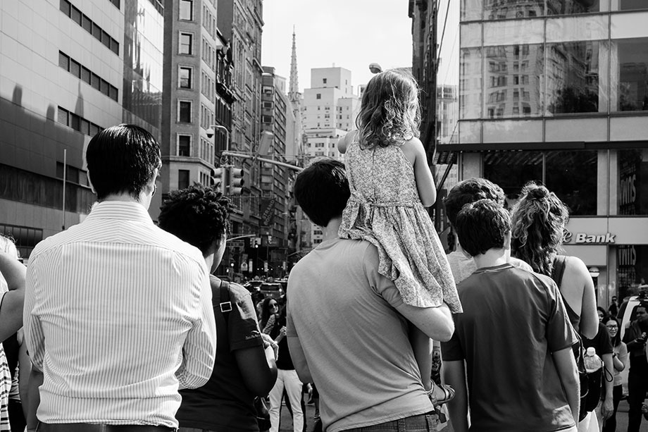 a girl sits on her father's shoulders to see a performance in Union Square