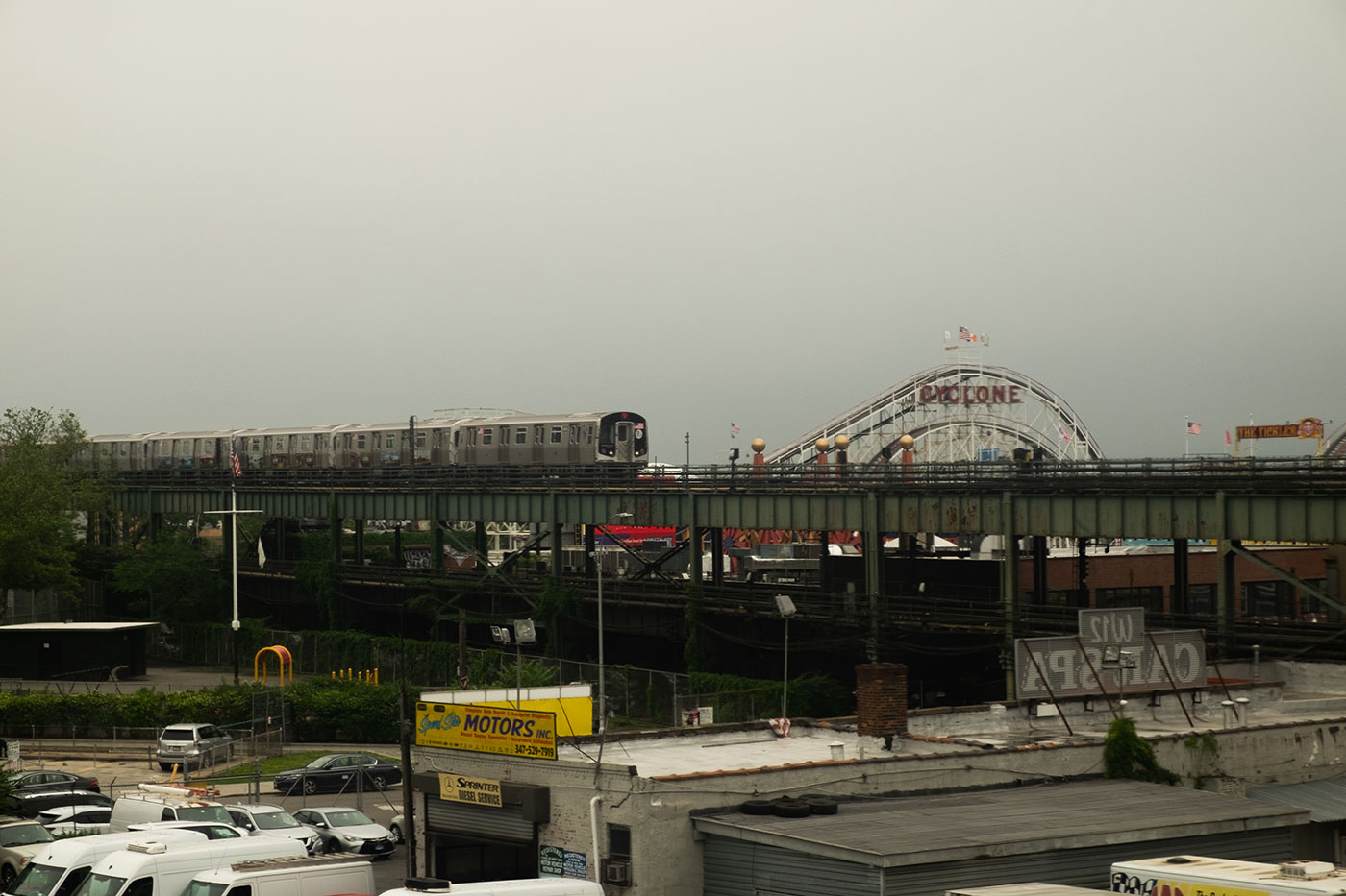 a train on an elevated rail line passes the Coney Island Cyclone