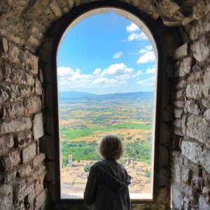boy looking out window in Italy