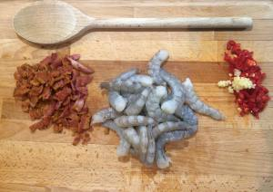 Shot showing the cooked and chopped bacon, the raw prawns and the chopped garlic and chilli.