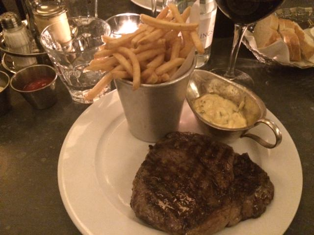 Shot showing grilled rib eye, béarnaise sauce, a small bucket of frites and a glass of red wine in candlelight.