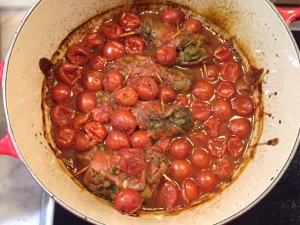 Close up of the cooked braciole in the pot surrounded by the cherry tomato sauce.