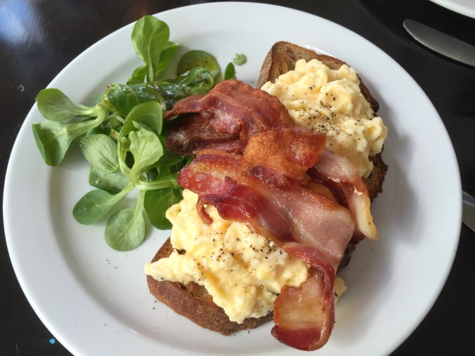 Shot of scrambled eggs and bacon on sourdough toast, delicious!