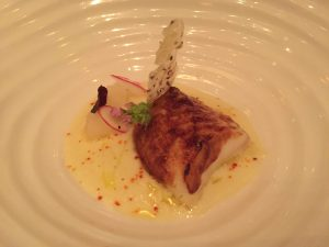 Shot of the delicate miso marinated black cod surrounded by yuzu sauce and daikon puree