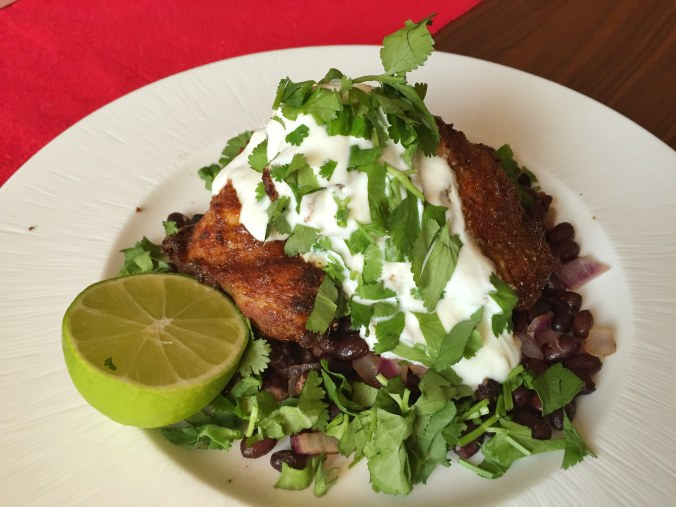 Chicken thighs piled high on black beans, topped with Greek yoghurt and coriander
