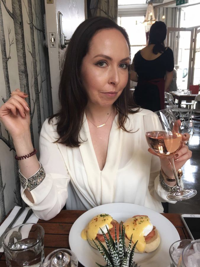 The blog's author, posing with a glass of wine and her Eggs Royale at The Jam Tree Chelsea