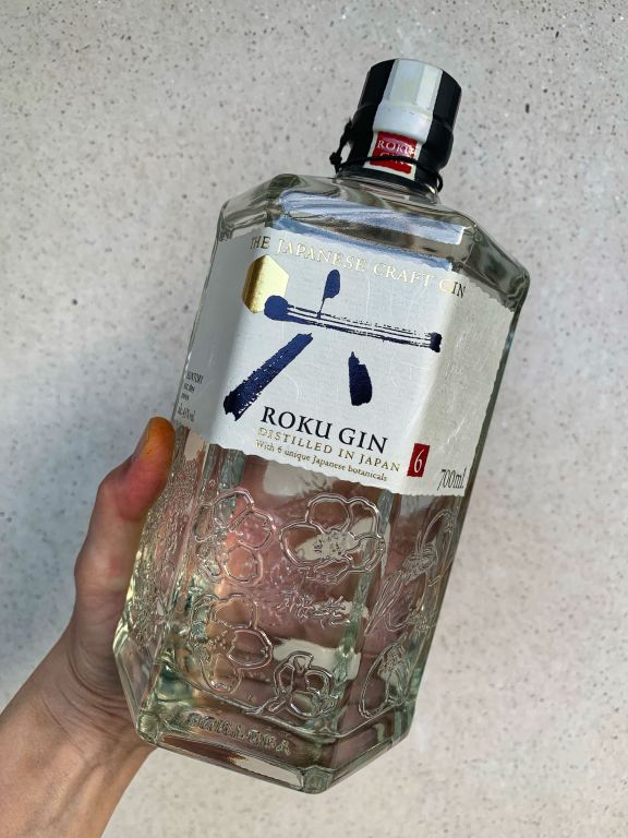 Photograph of the bottle of Roku gin, with the 6 sides clearly visible and the label on display. The glass is clear, the label is off white and texture and the Japanese font is black and gold.
