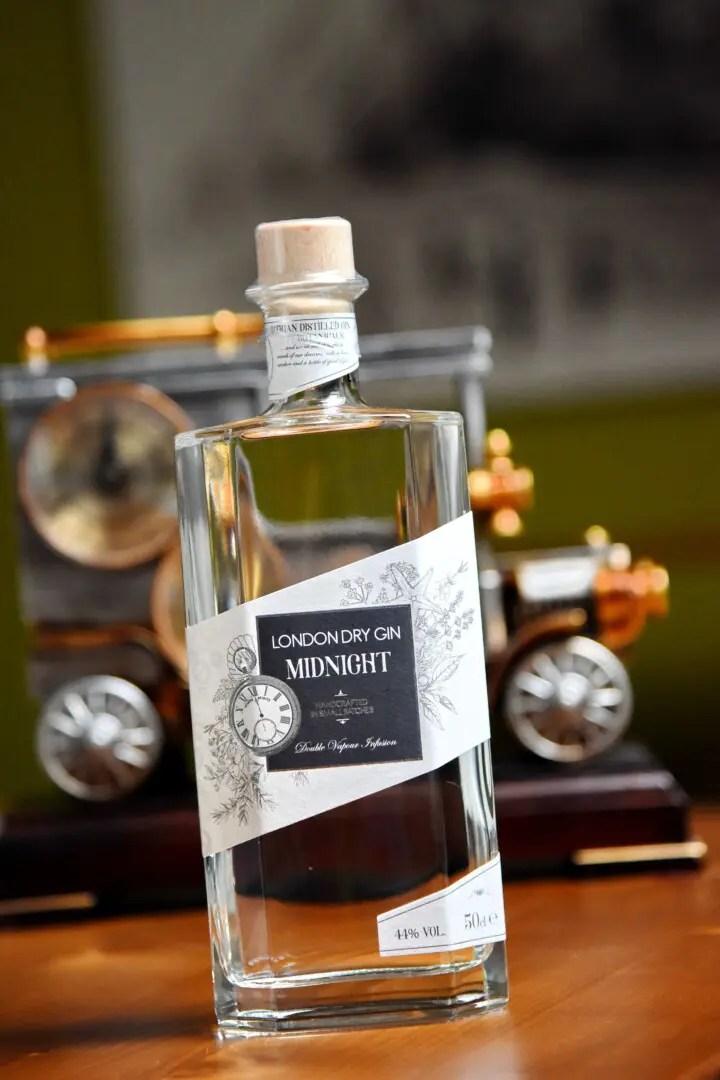 Billede af en flaske Imagine Spirits Midnight Gin med urværk i baggrunden