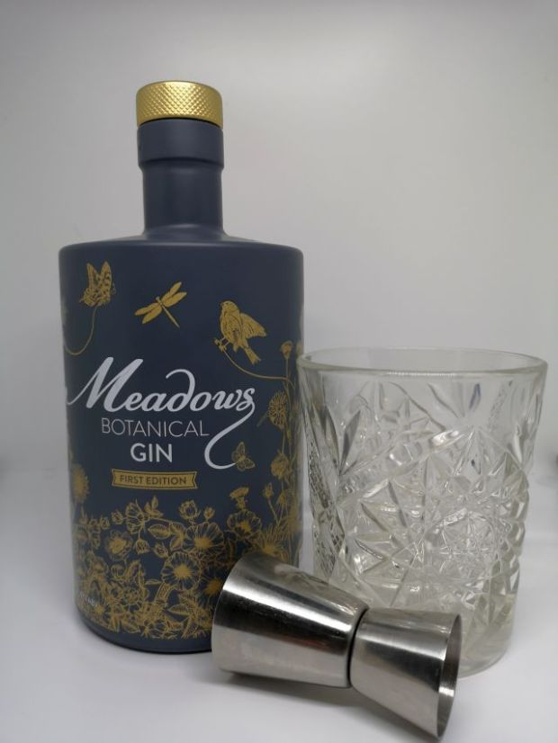 Image of a grey bottle decorated with gold flowers and birds, alongside a silver jigger and a short cut crystal glass containing gin, with a white background.