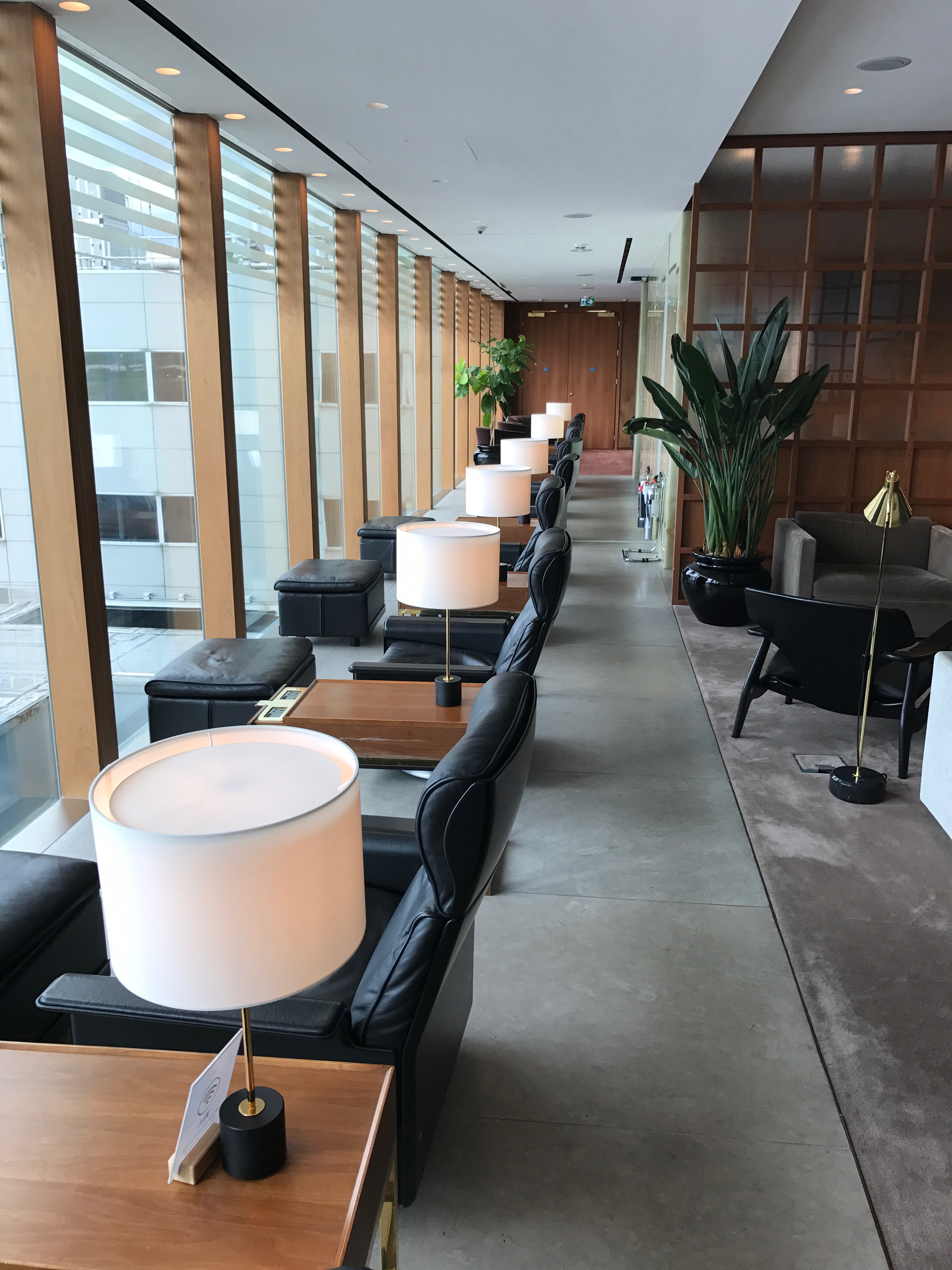 a row of black arm chairs and white lamps