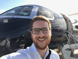 Ginger Travel Guru in front of a Surf Air private jet