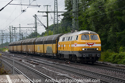 In the bright yellow of H F Wiebe Class 216 number 216 032-3 hauls a rake of car carriers northbound through Hamburg Harburg station on the 19th of July 2012