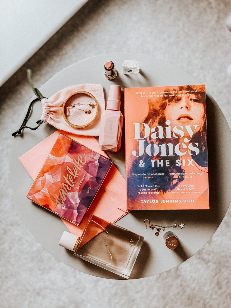 Daisy Jones & The Six book on a grey table with various pink props.