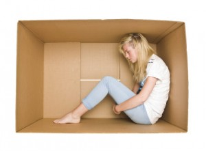 Woman siting in a cardboard box isolated on white background emozionale MODELLAMENTO EMOZIONALE paura futuro 300x221