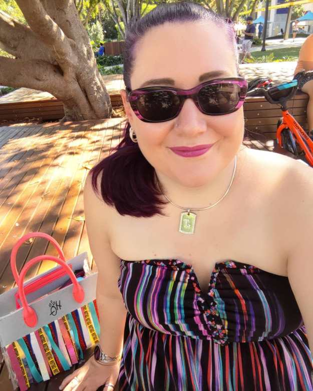 Photo of Jess dodson, sitting on a bench, with a Harley Quinn handbag beside her, wearing a stripey strapless dress and sunglasses; taken in March 2021