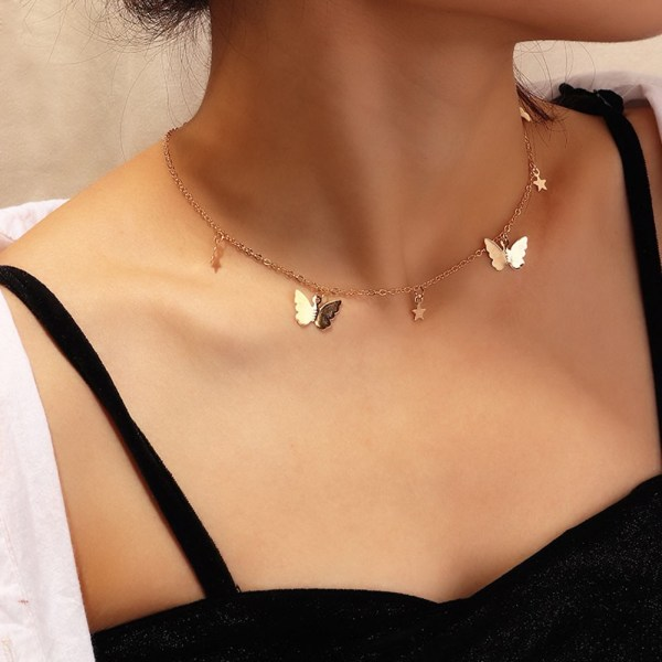 A photo showing a gold necklace with butterfly and stars for pendants worn by a model. The photo is a close up of the jewelry.