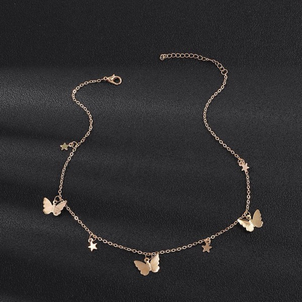 The photo shows the butterfly stars gold necklace with a black background. It is a close up image with the necklace sitting on top of a surface.