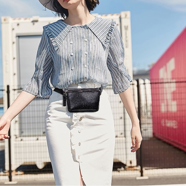 The photo shows an alligator patterned black waist bag worn by a model.