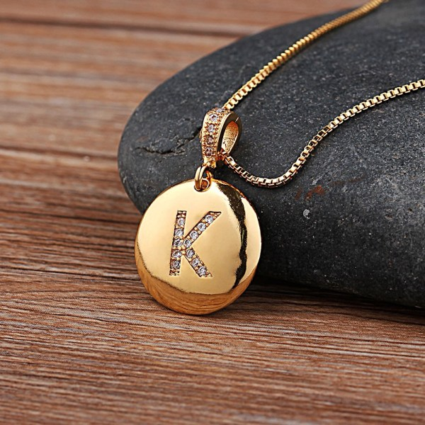 """A photo showing a close up of the pendant with the letter """"K"""" as an initial on a gold necklace."""