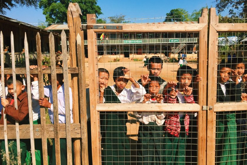 Indein kids watching soccer through school gate
