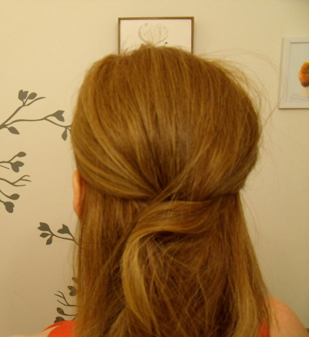 Bobby pins in place holding the hair half up.