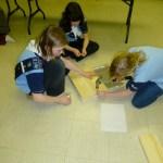 Kerri holding board, Amelia watching, Sophie hammering board